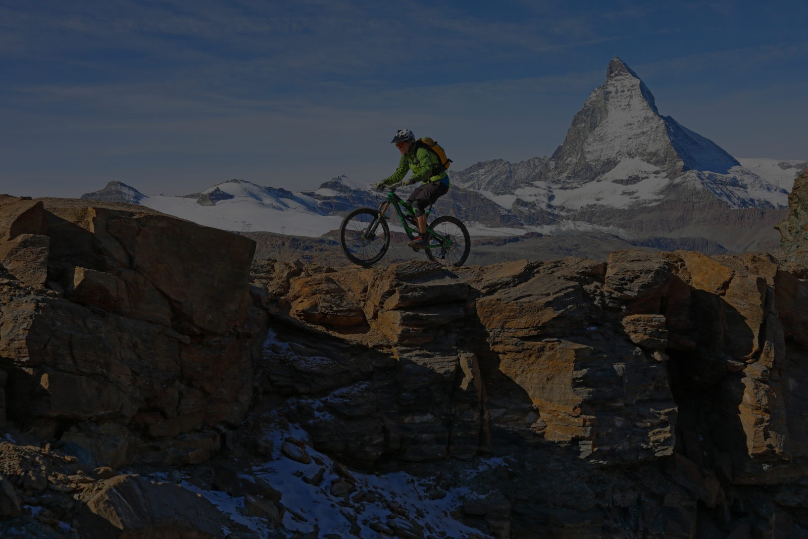 Young man mountain bikes along rock edge below the Matterhorn mountain